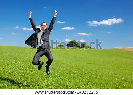 Excited businessman jumps high in the air cheering and celebrating a success or achievement in a green sunny field under a blue sky - stock photo
