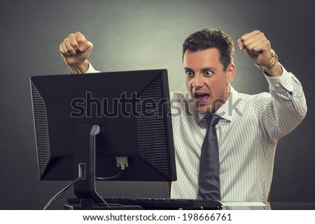 Excited businessman shouting of joy and gesturing with raised clenched fists over successful business deal in front of a computer over dark grey background. - stock photo