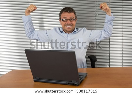 Excited businessman shouting of joy and gesturing with raised clenched fists over successful business deal in front of a computer over dark grey background.