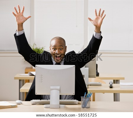 Excited businessman sitting at desk cheering and celebrating his success - stock photo