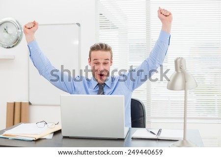 Excited businessman with arms up cheering in his office - stock photo
