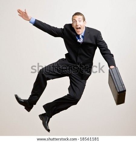 Excited businessman with briefcase jumping in mid-air cheering and celebrating his success - stock photo