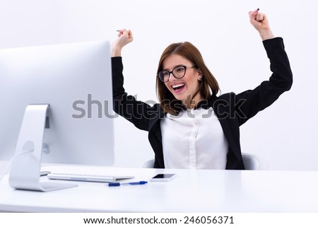 Excited businesswoman rejoicing at her success cheering and raising her fists in the air - stock photo
