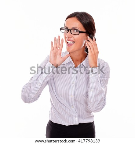 Excited businesswoman speaking on cell phone while looking at camera and making a gesture with one hand wearing her straight hair back and a button down shirt on a white background