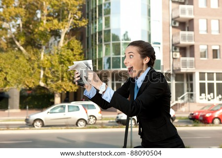 excited businesswoman with newspaper, excellent news - stock photo