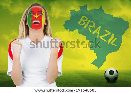 Excited cameroon fan in face paint cheering against football pitch with brazil outline and text - stock photo