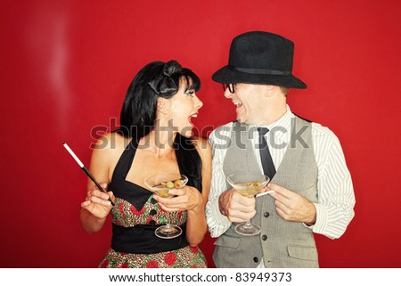 Excited Caucasian couple enjoy martini and cigarette over maroon background - stock photo