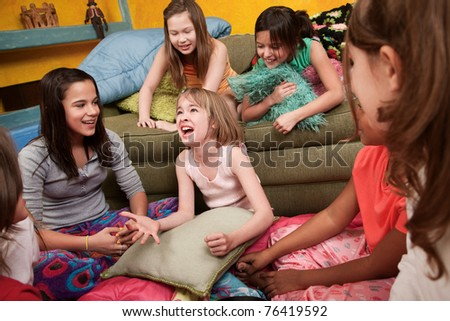 Excited Caucasian girl with her happy friends at a sleepover - stock photo