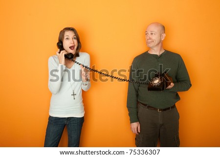 Excited Caucasian woman on telephone call with a middle-aged man on orange background - stock photo