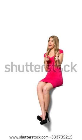 Excited Caucasian young woman with long light blond hair in evening outfit makes finger gun - Isolated - stock photo