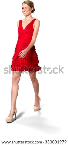 Excited Caucasian young woman with medium blond hair in evening outfit walking - Isolated