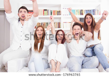 excited cheerful friends watching football game on tv - stock photo