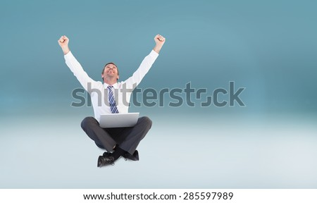 Excited cheering businessman sitting using his laptop against blue vignette background