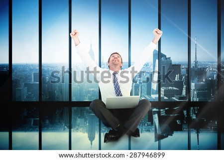 Excited cheering businessman sitting using his laptop against room with large window looking on city - stock photo