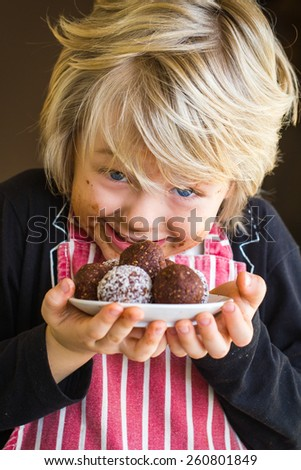 Excited child with messy face showing homemade chocolate balls - stock photo