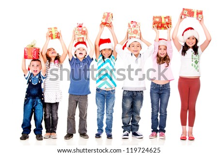 Excited children holding Christmas gifts with arms up - isolated over white - stock photo