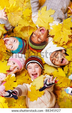 Excited children in yellow leaves - stock photo