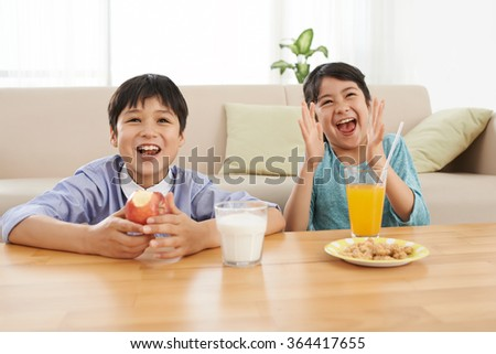 Excited children watching tv when eating breakfast - stock photo