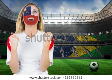 Excited chile fan in face paint cheering against large football stadium with brasilian fans - stock photo