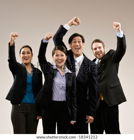 Excited co-workers cheering and celebrating their success - stock photo