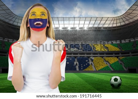 Excited colombia fan in face paint cheering against large football stadium with brasilian fans - stock photo