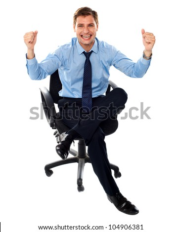 Excited corporate male sitting on chair with his arms up