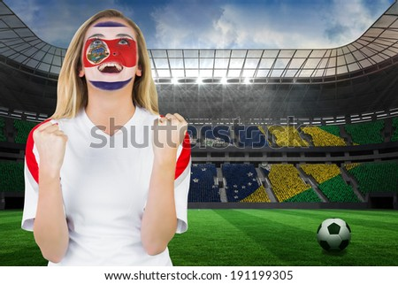 Excited costa rica fan in face paint cheering against large football stadium with brasilian fans - stock photo