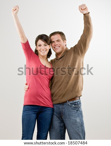 Excited couple cheering and celebrating their success - stock photo