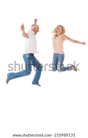 Excited couple cheering and jumping on white background - stock photo