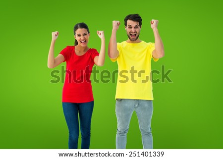 Excited couple cheering in red and yellow tshirts against green vignette - stock photo