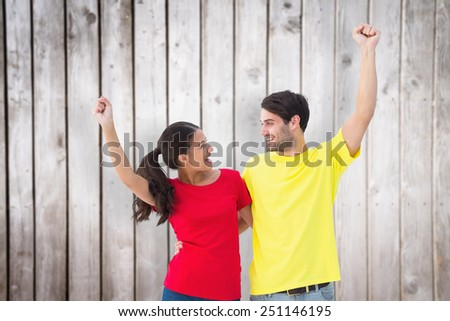 Excited couple cheering in red and yellow tshirts against wooden planks - stock photo