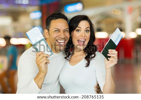 excited couple going on a vacation and holding passport boarding pass at airport - stock photo