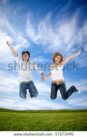 Excited couple holding hands and jumping outdoors - stock photo