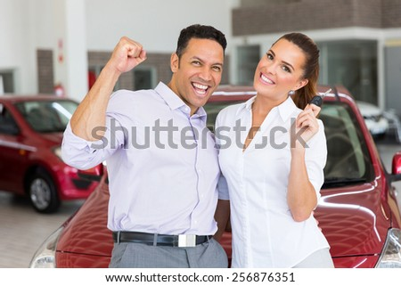 excited couple just bought a new car from dealership - stock photo
