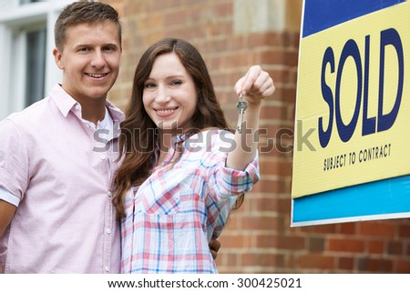Excited Couple Outside New Home Holding Keys - stock photo