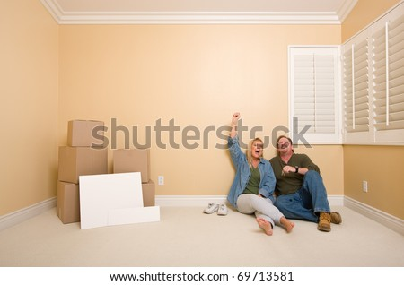 Excited Couple Relaxing on Floor Near Boxes and Blank Real Estate Signs in Empty Room