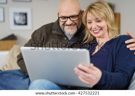 Excited couple seated on couch in living room holding and reading their tablet near wall with framed photos - stock photo