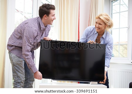 Excited Couple Setting Up New Television At Home - stock photo
