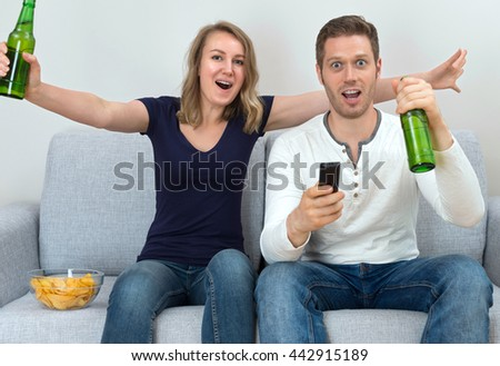Excited couple watching sports match on tv. - stock photo