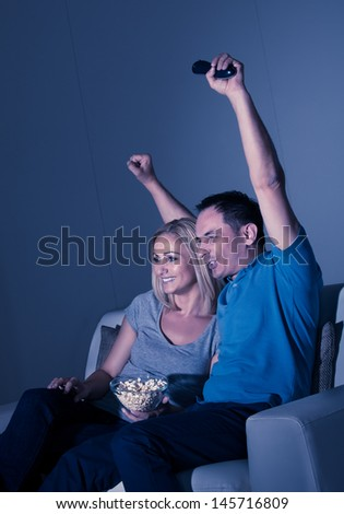 Excited Couple Watching Television And Eating Popcorn - stock photo