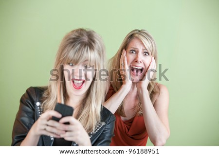 Excited daughter texting with shocked mom behind her over green background - stock photo