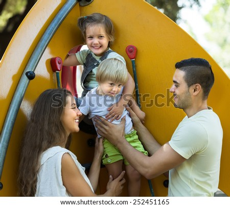 Excited daughters climbing at playground ladder with young parents - stock photo