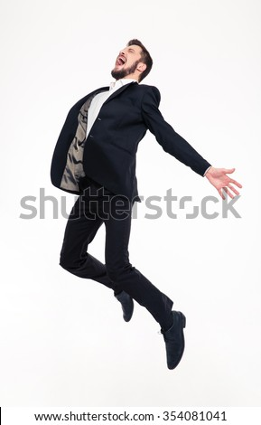 Excited elated happy young business man with beard in classic suit jumping and shouting over white background - stock photo