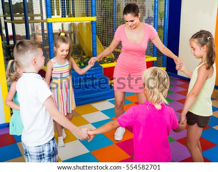 excited european children dancing with teacher to music in class at school