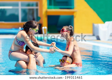 excited family having fun in pool, water fight - stock photo