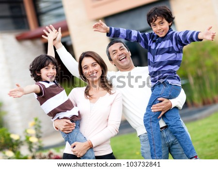 Excited family having fun outdoors with arms up - stock photo