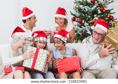 Excited family swapping christmas presents on the couch