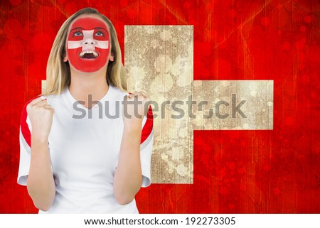 Excited fan in swiss face paint cheering against switzerland flag in grunge effect - stock photo