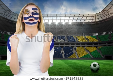 Excited fan in uruguay face paint cheering against large football stadium with brasilian fans - stock photo