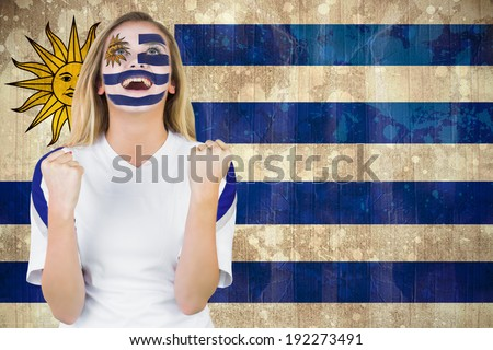 Excited fan in uruguay face paint cheering against uruguay flag in grunge effect - stock photo